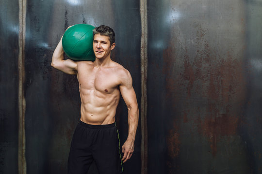 Portrait of shirtless man holding ball in gym