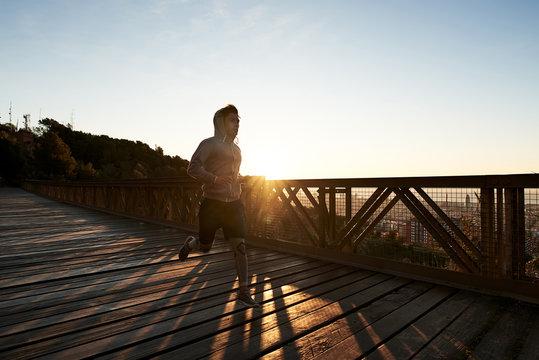 Young man running on boardwalk