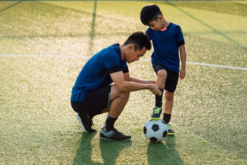 Father helping son dressing up in soccer socks