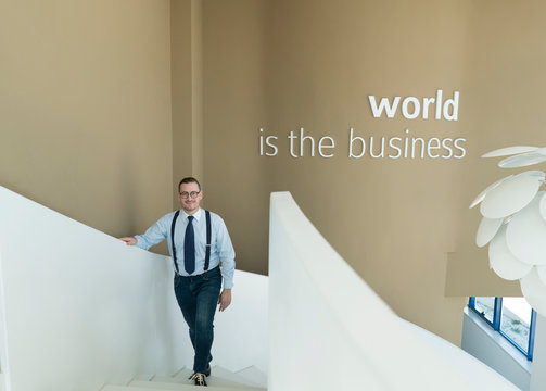 Portrait of confident businessman walking up stairs in modern office