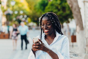 Portrait of a young African American girl with pigtails . The girl is talking on a mobile phone, smiling. Sunny day.