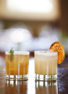 Whiskey Cocktail and Grapefruit Margarita mixed drinks on table