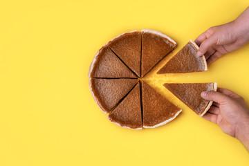 Hands taking pie slices. Eating pumpkin pie