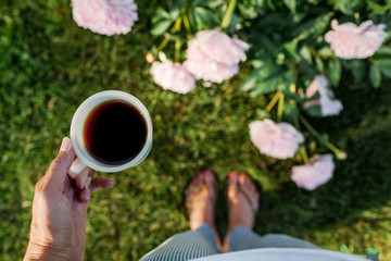 woman holding a cup of coffee early in the morning in a peony garden