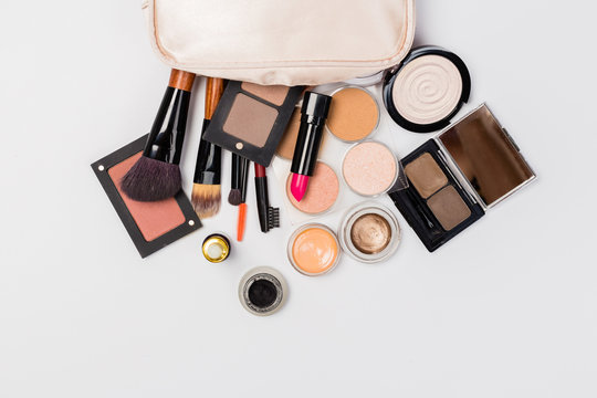 A pink makeup bag with cosmetic beauty products spilling out on to a light  background, with empty space at side