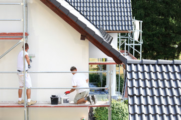 Obraz Malowanie wałkiem elewacji budynku na rusztowaniu. - fototapety do salonu