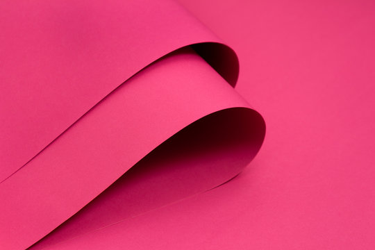 Folded pink paper on pink background