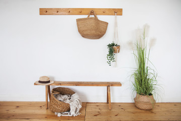 Modern interior hallway in the Scandinavian style. Wooden bench, straw bags, straw basket, straw hat