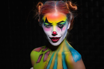 Lovely young woman with a face painting clown.