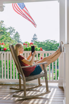 Teen On Tablet Relaxing on Porch