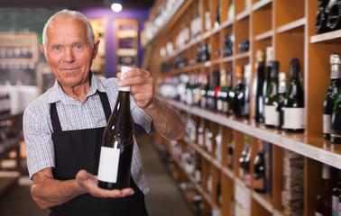 Confident older male owner of wine shop