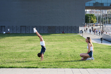 Blonde girl doing handstand with sister watching.