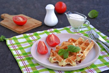 Savory zucchini waffles on a white plate on a dark concrete background. Served with ranch dressing and fresh tomato. Healthy food.