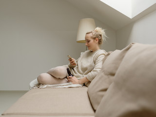 Chilling woman with beer and phone on sofa