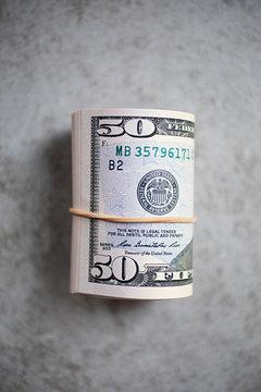 Rolled up $50 USA dollar bills on grey background