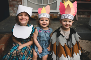 Smiley children play dress up for Thanksgiving