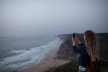 Woman doing pictures with her phone at coast