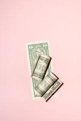 US Dollar Bills On Pink Background