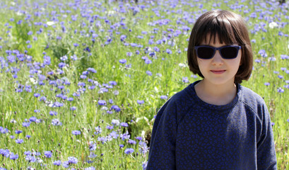 happy child over a sunny rural cornflower floral field background