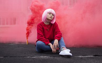 Female hipster sitting near red smoke Wall mural
