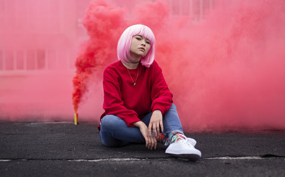 Female hipster sitting near red smoke