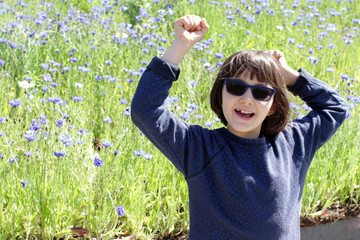 joyful child with blue sunglasses laughing for being in nature