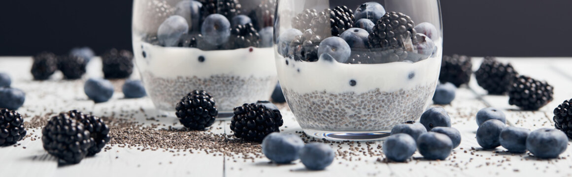panoramic shot of yogurt with chia seeds and berries in glasses near scattered seeds, blueberries and blackberries on white table isolated on black