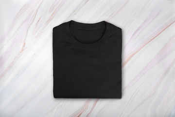 Flat lay of black folded tshirt on marble background. Blank black cotton tee-shirt on natural marble texture. Top view