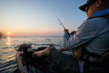 Papiers peints Peche Young Man Kayak Fishing at Sunrise in Canada