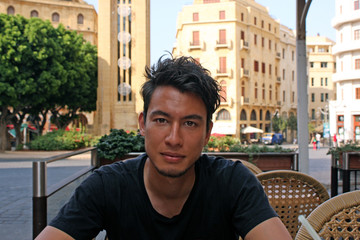 Young man with wild dark hair in a cafe looking at the camera