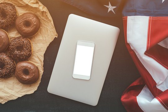 Smart phone mock up with chocolate donuts and USA flag
