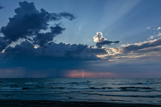 Extreme weather with sunrise and rays of light but also storm clouds with rain over the sea. Thunderstorm and lightning against dramatic colorful sky