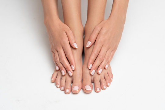Perfectly done manicure and pedicure on white background.