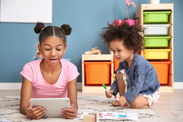 Cute African-American girl with tablet computer watching cartoons at home
