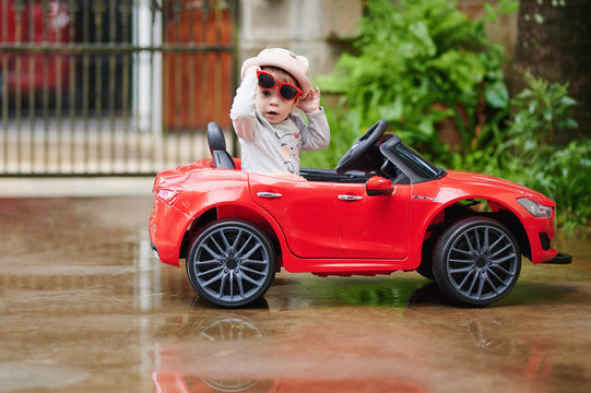Pretty baby girl in red toy car