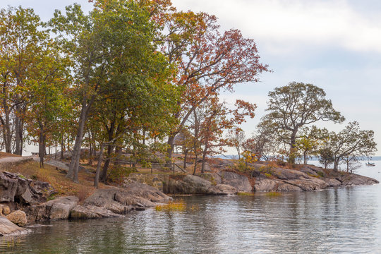 The Manor park of Larchmont on a autumn landscape with calm ocean water