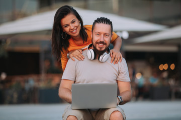 Young happy couple using laptop outdoors