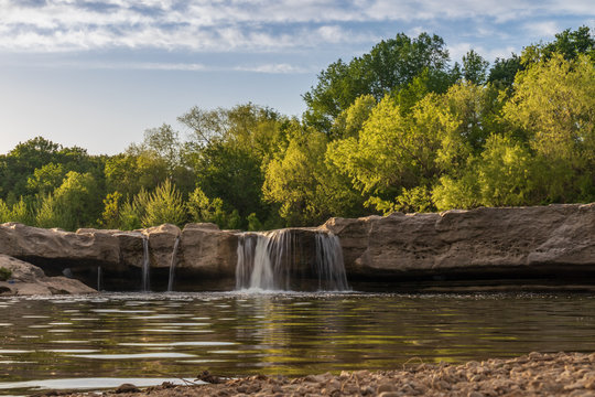 Waterfall at McKinney Falls State Park with large trees and blue sky background, Austin, Texas
