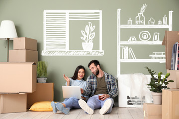 Happy couple with laptop imagining interior of new house Wall mural
