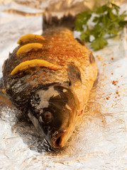 Fresh sea bass. Mediterranean fish, baked entirely in a coal stove with herbs and lemon