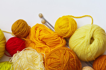 Colorful yellow balls of yarn for hand knitting and needles on a white background. On top empty space for text. Flat lay, close up. Crafts and Hobbies