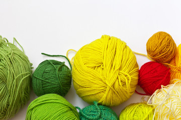 Needlework. Colorful  balls of yarn for hand knitting on a white background. On top empty space for text. Flat lay, close up. Crafts and Hobbies
