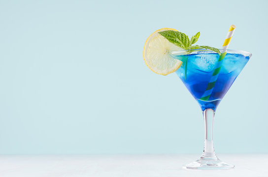 Bright summer fresh blue fruit cocktail with blue curacao liquor, ice cubes, lemon slice, green mint in pastel mint color interior on white wood board.