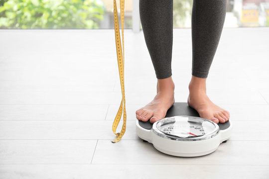 Woman with tape standing on scales indoors, space for text. Overweight problem