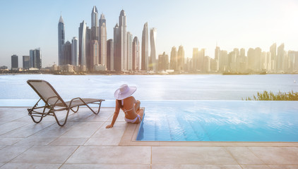 Recess Fitting Dubai Beautiful panorama of Dubai Marina skyline in a background with a pool, deck chair and woman with a white hat.