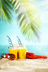 Table background with orange ice juice in a glass on a wooden table top with beautiful blue sky and...