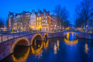 Wall Mural - Dutch buildings in Amsterdam at night in Netherlands