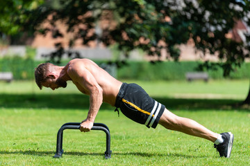 Fit athlete man doing push up with push-up bars on the floor, outdoor  sport and training in grass concepts