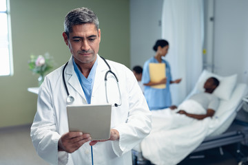 Male doctor using digital tablet in the ward at hospital