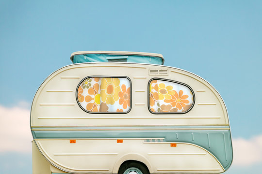 Vintage seventies white caravan in front of a blue sky with clouds